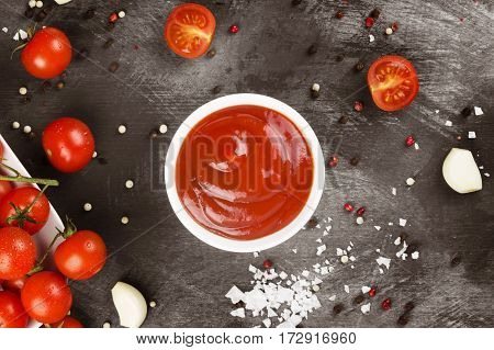 Tomato Sauce In White Bowl, Spice And Cherry Tomatoes On A Dark Background. Top View. Toning.