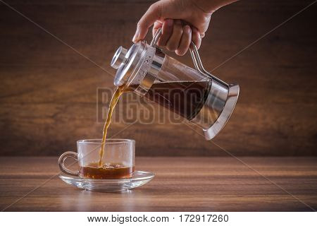 Pouring the hot water of coffee from french press into the glass