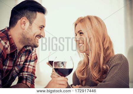 Close up of a young couple enjoying wine at home.They are sitting close to each other and drinking red wine.