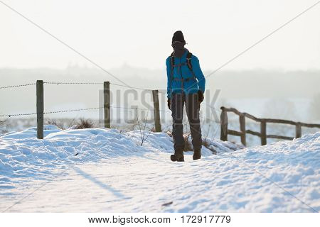 Man Walking On Path Covered In Snow.