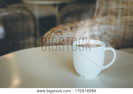 Cup of coffee on wooden table in coffee shop. Coffee break in morning selective focus.