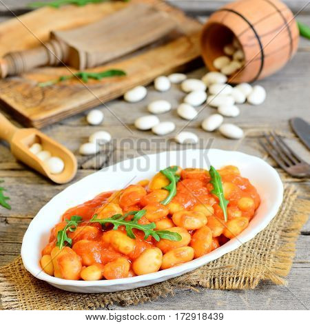 Delicious baked beans with carrots, tomatoes and fresh arugula on a plate and on a wooden table. Slow cooked baked beans recipe. Rustic style. Closeup