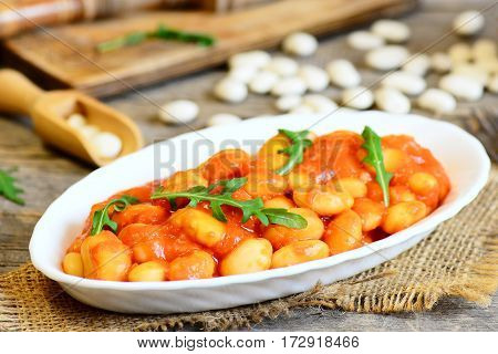 Spicy baked beans with tomato sauce served with fresh arugula on a plate. Slow cooked home baked beans recipe. Vegetarian side dish. Rustic style. Closeup
