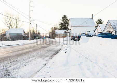 Houses and cars covered in snow in sub-zero conditions in Canadian country town in winter