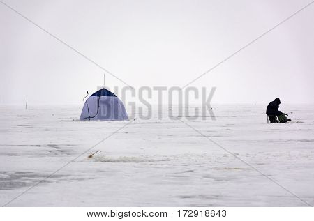 black fisherman in warm clothes sitting on the ice hole tentfishing rod screws winter day Bay sea snow white