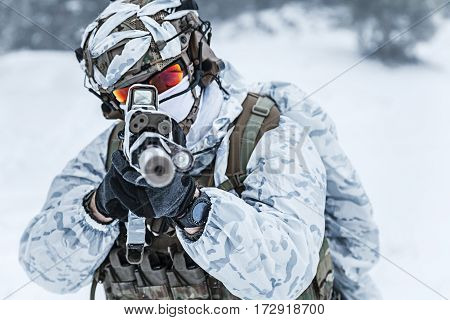Winter arctic mountains warfare. Action in cold conditions. Trooper with weapons in forest somewhere above the Arctic Circle, pointing at camera