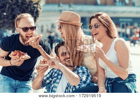 Friends eating pizza.They are enjoying togethereating pizza and having fun.