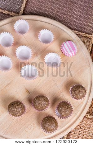 Chocolate Balls In Paper Baskets On The Wooden Board