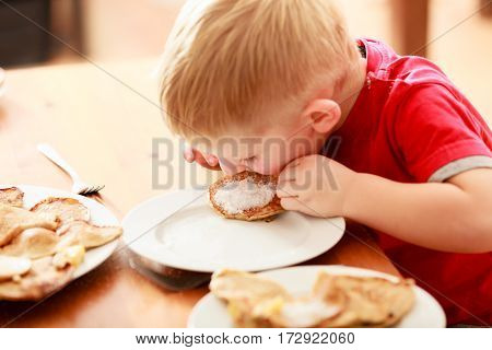 Morning routine in family healthy diet for children concept. Little boy eating pancakes for breaktfast