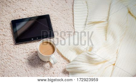 Coffee. A cup of coffee or tea tablet knitted blanket. Warm cozy home atmosphere.
