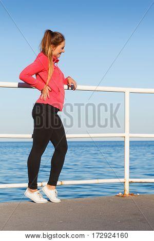 Woman In Sportswear Standing On Dyke By Sea