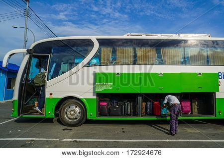 Menumbok,Sabah-Aug 19,2016:The bus driver checking luggage compartment on bus in Menumbok Terminal Bus before heading to Kota Kinabalu,Sabah Land Below The Wind.