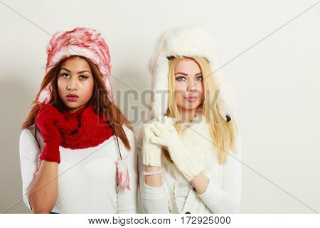 Fashion winter outfit concept. Two girls blonde and mulatto in warm red white clothing portrait. Attractive women wearing fur caps scarfs gloves.