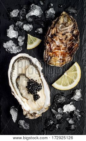 Oysters with black sturgeon caviar and lemon on black slate stone background. Top view flat lay
