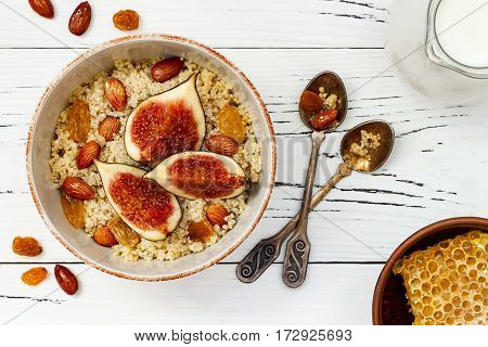 Gluten free amaranth and quinoa porridge breakfast bowl with figs caramelized almonds raisins and honey over rustic white table. Top view overhead flat lay. Copy space
