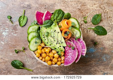 Vegan detox Buddha bowl recipe with avocado carrots spinach chickpeas and radishes. Top view flat lay copy space