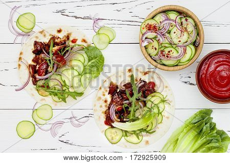 Korean slow cooked beef tacos with asian cucumber slaw and sriracha ketchup. Top view flat lay copy space
