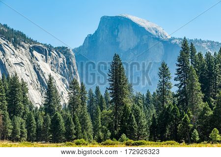 Half Dome is a granite dome at the eastern end of Yosemite Valley in Yosemite National Park California. It is a well-known rock formation in the park named for its distinct shape. One side is a sheer face while the other three sides are smooth and round