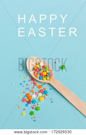 Easter decoration wooden spoon with colored sugar ingredients on a light blue background minimal design with text vertical image