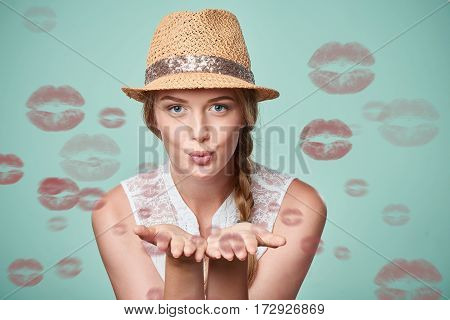 Beautiful woman wearing summer straw fedora hat blowing a kisses
