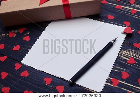 High side view of blank paper sheet for copy space and gift box. Flat lay background with small red hearts