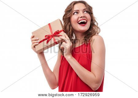 Close-up of pretty woman in red dress isolated over white background with a copy space. Woman holding a present box