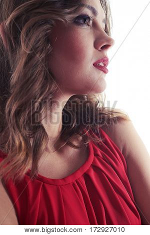 Side view of dreamy female with evening make-up gazing sideward. Dazzling look somewhere. Young Caucasian woman posing at the camera