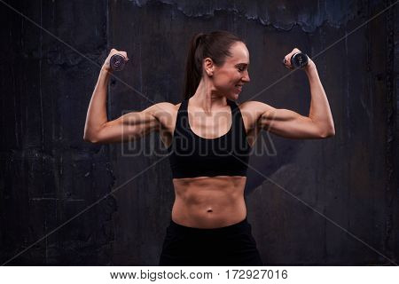 Mid shot of gorgeous long-haired brunette with two dumbbells posing at the camera. Wearing sportswear, standing isolated against rough grey wall
