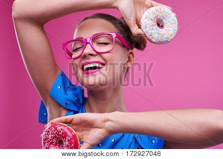Extreme close-up of elated girl with two doughnuts poses at the camera. Trendy girl in bright outfit closed eyes
