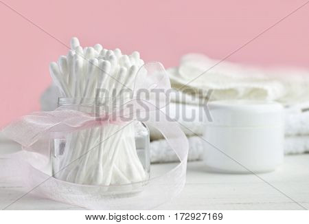 White plastic cotton sticks in glass jar decorated with bow, bathroom toiletries, pink backdrop, soft focus. Daily beauty routines.