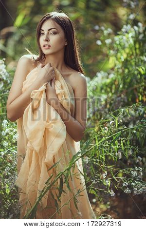 Beautiful young brunette woman portrait in flower meadow smiling and looking at camera. Girl holding cloth and hiding her naked perfect body