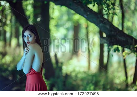 Wonderful sexy fashion model walking in a fantastical forest by footpath.Mystical portrait of sensual seductive woman with naked back in luxury long red dress posing against bokeh trees background. Multi-racial Asian Caucasian girl. Fashionable toning. Cr