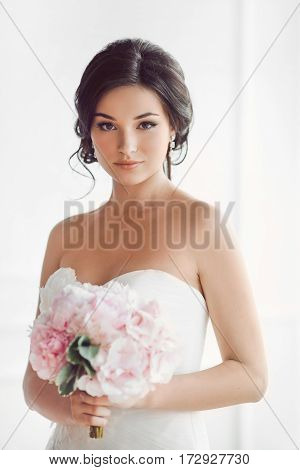 Beauty portrait of bride wearing wedding dress with feathers with luxury delight make-up and hairstyle, studio indoor photo. Young attractive multi-racial Asian Caucasian model with pink bouquet of flowers. Smiling beautiful young woman like a bride again