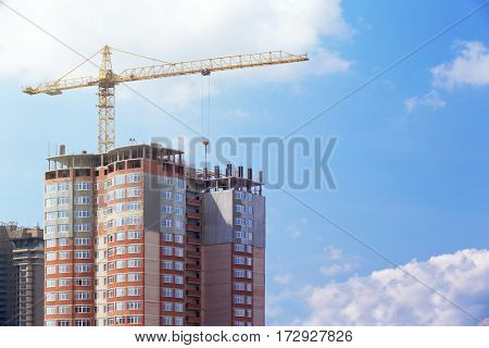 Construction crane and unfinished building with blue sky on background
