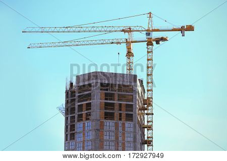 Construction cranes and unfinished building with blue sky on background
