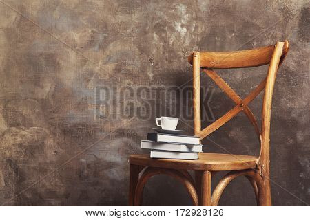 Stack of books on chair against gray wall background