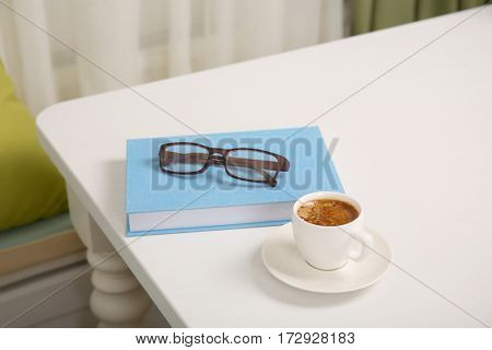 Blue covered book and cup of coffee on white wooden table