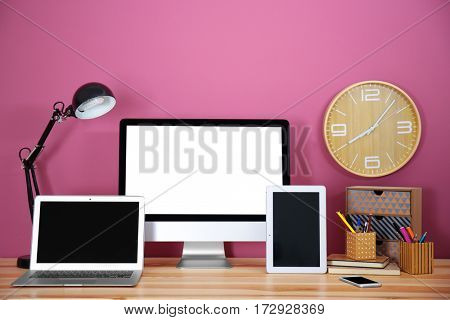 Computer display, laptop, tablet and smart phone on wooden table against color wall