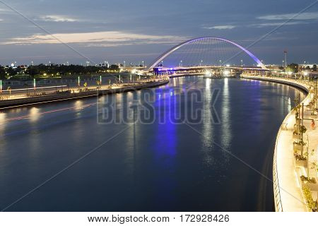 Dubai Water Canal and Arch Bridge illuminated at night. United Arab Emirates Middle East