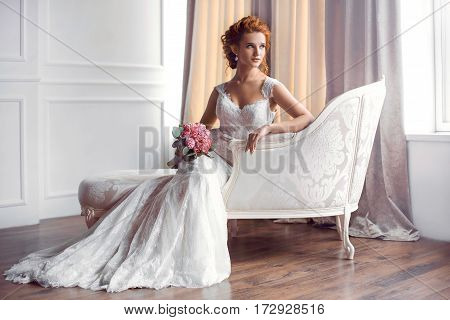 Bride in beautiful dress sitting on sofa indoors with bouquet of flowers in white studio interior like at home. Trendy wedding style shot in full length. Young attractive caucasian red hair model like a bride against big window tender resting.