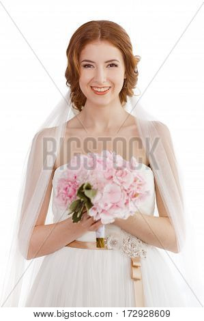 Studio shot of young beautiful smiling bride against white isolated background. Gorgeous luxury woman in white wedding dress, veil with classical make-up and hairstyle holding bouquet of flowers