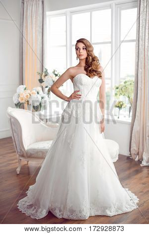 Wedding fashion bride. Perfect wedding white dress make-up and hairstyle. Gorgeous brunette model posing indoors
