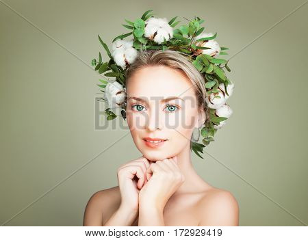 Cute Woman Fashion Model on Green Background. Spa Model with Green Leaves and Flowers