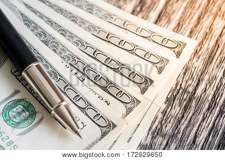 One hundred dollar bills and pen on the old wooden.