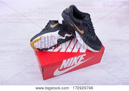 BURGAS, BULGARIA - DECEMBER 30, 2016: Nike Air MAX women's shoes - sneakers in black, on white wooden background. Nike is a global sports clothes and running shoes retailer.