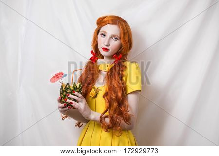 Red-haired girl with long hair in yellow dress standing with pineapple in hands on a white background. Red lips blue eyes. Bright unusual appearance.