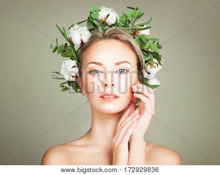 Beautiful Woman with Wreath of Organic Leaves and Cotton Flowers. Spa Model with Nude Makeup Face Closeup
