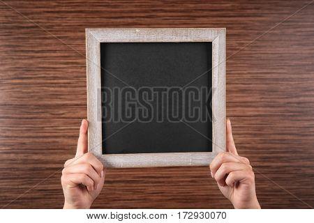 Female hands holding empty blackboard on wooden background