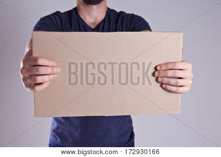 Man holding piece of cardboard with space for text on light background
