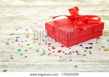 Birthday gift and colorful confetti on wooden background